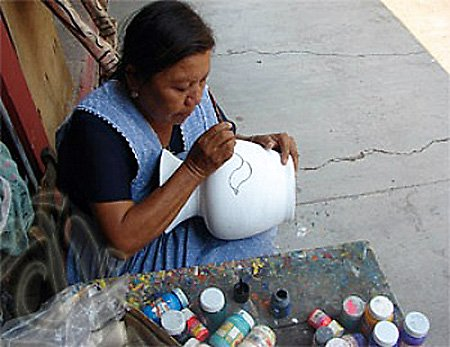 Artist painting clay vessel